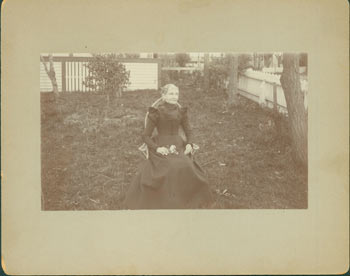 Photograph of seated elderly lady in black dress, holding flowers in her lap. 19th Century American Photographer.