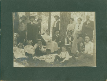 Photograph of a picnic in the woods with nine men, three women and four children total, seated and standing. 19th Century American Photographer.