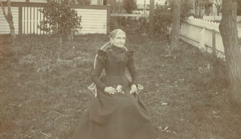 Monochrome Photograph of a woman seated in chair in backyard formally dressed (mourning wear?), holding flowers in her lap. 20th Century American Photographer.
