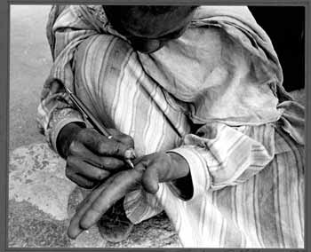 [Man Writing with a pen on his hand]. Gerda S. Mathan.