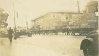 B&W Photograph of Intersection with Hay-Stacked Horse-Drawn Carriages and Packards. Early 20th...