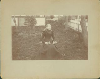 Photograph of seated elderly lady in black dress, holding flowers in her lap. 19th Century...