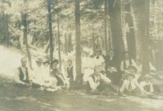 Photograph of a picnic in the woods, people seated below small American flag. 19th Century...