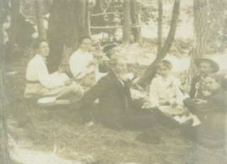 Photograph of a picnic in the woods with three men, three women and one boy, seated. 19th Century...