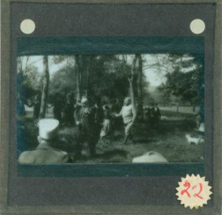 Glass Plate Negative depicting man playing fiddle in a meadow, surrounded by an audience with...