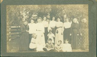 Black and White Photograph of a family, fourteen adults standing, five children seated and...